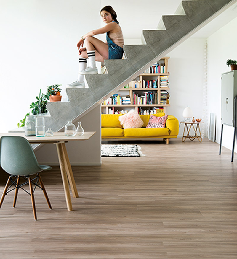 Meisje op trap op een vinylvloer wat is het verschil tussen vinyl en laminaat